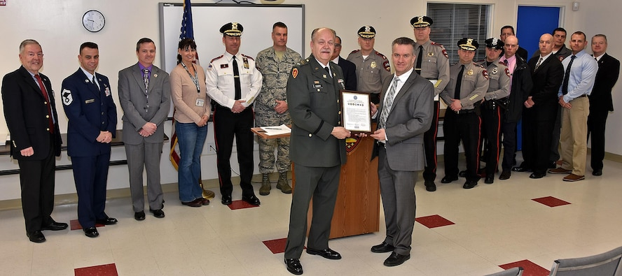 ESGR Volunteer Phil Albert presents the signed declaration of support to West Warwick Police Chief John Magiera