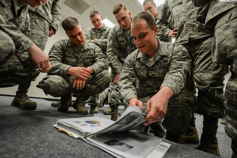 "Airmen huddle around a binder full of Air Force heritage pictures and stories inside the Airman Leadership School at Ellsworth Air Force Base, S.D., March 20, 2017. During a presentation by Robert Schilling, a former Airman and gunner on the AC-47 ""Spooky"" during the Vietnam War, students were able to flip through a binder of information about the aircraft, its crew and what they accomplished. (U.S. Air Force photo by Airman 1st Class Randahl J. Jenson)"