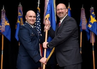 U.S. Air Force Col. Todd Hohn, 97th Air Mobility Wing commander, and Brian Bush, 97th Air Mobility Wing honorary commander and president of the Altus Chamber of Commerce, present the wing guidon during the Honorary Commander Induction Ceremony March 24, 2017, Altus Air Force Base, Oklahoma. Twenty-seven community members were inducted into the two-year program. (U.S. Air Force photo by Senior Airman Franklin R. Ramos/Released)