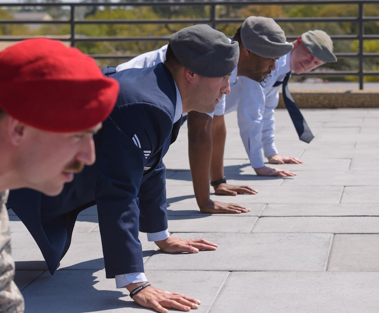 Senior Airman Matthew James, 335th Training Squadron student, leads graduates and guest in Memorial Pushups during a Special Operations Weather Apprentice Course graduation ceremony at the Weather Training Complex, March 22, 2017, on Keesler Air Force Base, Miss. At his graduation James received his Gray Beret. (U.S. Air Force photo by Andre' Askew)