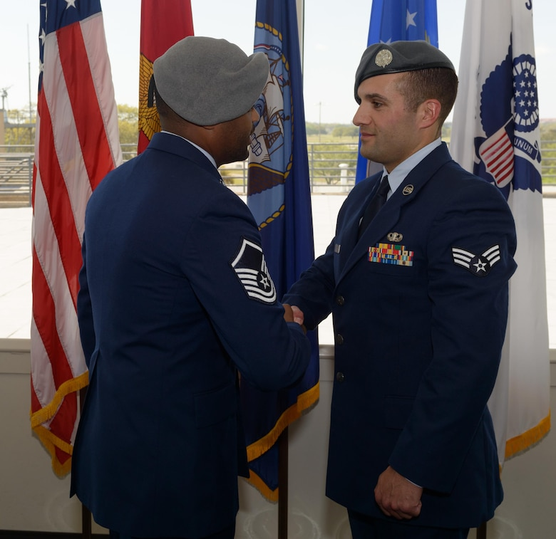 A Battlefield Airman congratulates Senior Airman Matthew James, 335th Training Squadron student, on graduating from the Special Operations Weather Apprentice Course at the Weather Training Complex, March 22, 2017, on Keesler Air Force Base, Miss. At his graduation James received his Gray Beret. (U.S. Air Force photo by Andre' Askew)