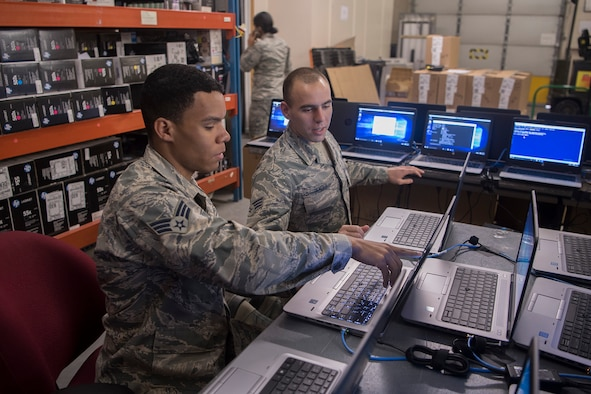 PETERSON AIR FORCE BASE, Colo. – Senior Airmen Jonathon Clayton, left, and Dylan Bender, 21st Communication Squadron client systems technicians, work together to bring new Windows 10 laptops into compliance with Air Force standards at Peterson Air Force Base, Colo., March 22, 2017. The Windows 10 roll out is part of a Department of Defense wide mandate to update all computers across all services. The 21st CS has been working extra shifts to ensure that mandate is met well ahead of schedule on April 1.  (U.S. Air Force photo by Steve Kotecki)