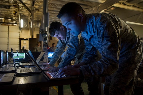 PETERSON AIR FORCE BASE, Colo. -- Senior Airman Jonathan Feiler, left, and SSgt. Shawn Erway, 21st Communication Squadron client service technicians, work to load new Windows 10 operating systems onto laptops for the 21st Space Wing at Peterson Air Force Base, Colo., March 22, 2017. The Windows 10 roll out is part of a Department of Defense-wide mandate to update all computers across all services. The 21st CS has been working extra shifts to ensure that mandate is met well ahead of schedule on April 1. (U.S. Air Force photo by Steve Kotecki)
