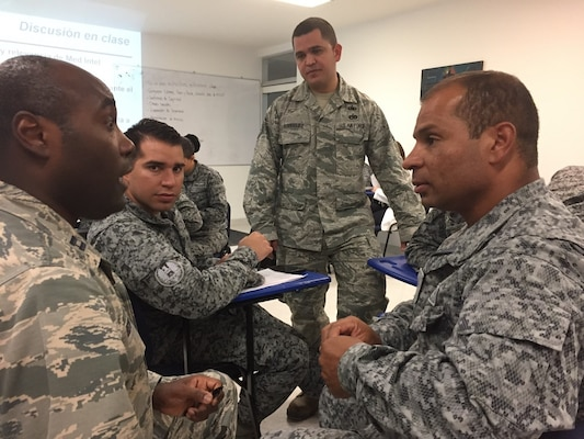 Tech. Sgt. Filberto Rodriguez, center, 571st Mobility Support Advisory Squadron Air Advisor, prepares to translate for an augmentee providing medical intelligence training to members of the Colombian Air Force in Bogota, Colombia. The 571st MSAS alongside Airmen from five other squadrons spent three weeks training the Colombian forces in air operations, aeromedical evacuation, propeller balance, zodiac rigging and medical intelligence courses. (Courtesy Photo)