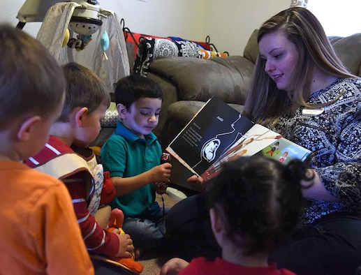 Liz Arrexi, 341st Force Support Squadron family child care home provider, right, reads a book to children March 24, 2017, at Malmstrom Air Force Base, Mont. Homes on base are licensed for only six children Air Force wide. (U.S. Air Force photo/Senior Airman Jaeda Tookes)