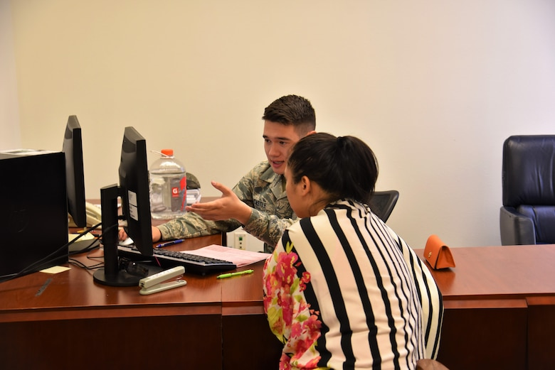 Senior Airman Michael Castle, 90th Missile Maintenance Squadron tax center volunteer, assists a customer in filing her taxes at F.E. Warren Air Force Base, Wyo., Mar. 23, 2017.  The tax center's goal is to help service members, retirees and dependents file their taxes free of charge. Operating hours are Monday through Friday by appointment only until April 18, for more information please contact the Tax Center at 773-5829. (U.S. Air Force photo by 2nd Lt. Nikita Thorpe)