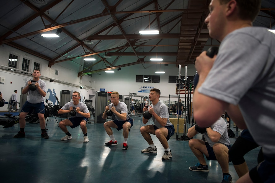 Members of the 790th Missile Security Forces Squadron perform kettlebell squats during squadron physical training on F.E. Warren Air Force Base, Wyo., Feb. 1, 2017. The 790th MSFS performs a multitude of workouts focusing on cardio and muscular fitness. (U.S. Air Force photo by Staff Sgt. Christopher Ruano)