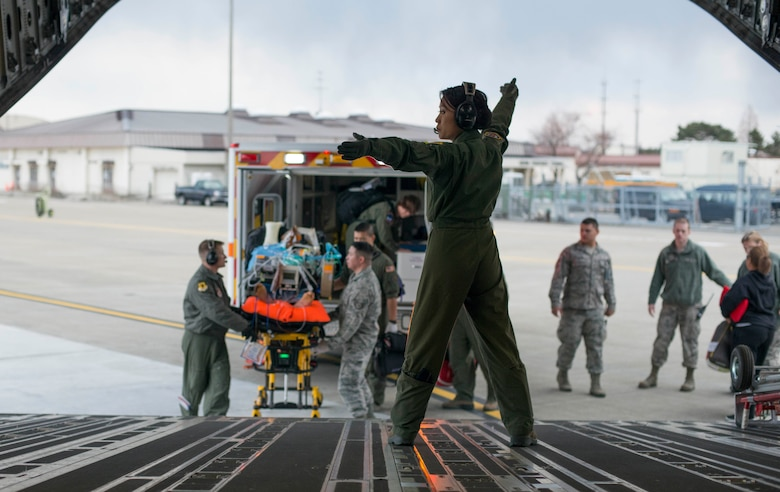 U.S. Air Force Capt. Lynn Nguyen, an 18th Aeromedical Evacuation Squadron flight nurse, guides medical personnel onto a C-17 Globemaster III during an aeromedical evacuation at Misawa Air Base, Japan, March 22, 2017. (U.S. Air Force photo by Senior Airman Brittany A. Chase)