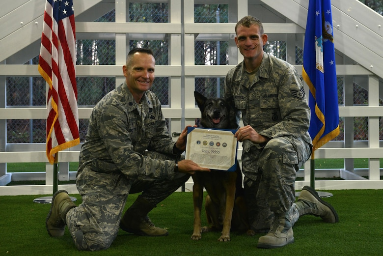 U.S. Air Force Lt. Col. Garon Shelton, 20th Security Forces Squadron (SFS) commander, left, awards Jony, a retiring 20th SFS military working dog (MWD), center, a certificate of meritorious service, while Staff Sgt. Brian Claypool, 20th SFS MWD handler, right, holds the certificate at Shaw Air Force Base, S.C., March 22, 2017. Jony retired after nine years of service due to a compressed disc in his spine. (U.S. Air Force photo by Airman 1st Class Destinee Sweeney)