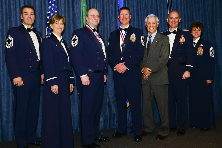 """Fairchild leadership and Retired Lt. Col. Barry Bridger, a survivor of the """"Hanoi Hilton"""" prison camp in Vietnam, pose for a photo with the newly selected Chief Master Sgts. Chad Madore and Shane Sweeney during the Chief Recognition Ceremony Mar. 25, 2017, at Fairchild Air Force Base, Washington. The ceremony consisted of a medallion and a candle lighting ceremony where they lit nine candles that represented each enlisted grade in the Air Force. (U.S. Air Force photo/Senior Airman Janelle Patiño)"""