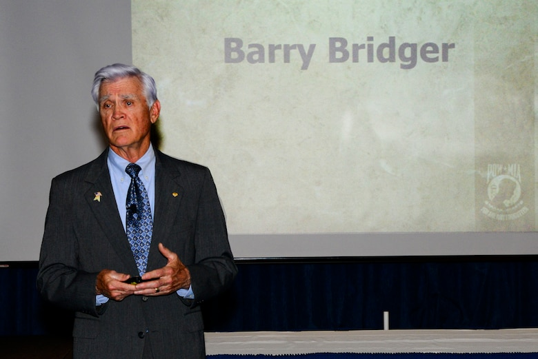 """Retired Lt. Col. Barry Bridger, a survivor of the """"Hanoi Hilton"""" prison camp in Vietnam, speaks with the audience about his experiences as a prisoner of war for six years during the Chief Recognition Ceremony Mar. 25, 2017, at Fairchild Air Force Base, Washington. Bridger was shot down over Son Tay, North Vietnam, by a surface-to-air missile and was captured by the North Vietnamese. (U.S. Air Force photo/Senior Airman Janelle Patiño)"""