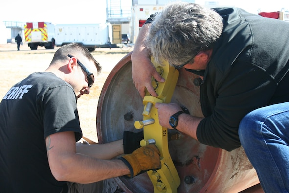 Richard Heaverlo, El Paso County Office of Emergency Management hazardous materials trainer, right, and Deputy Scott Stephens, El Paso County Sheriff's Office, seal a 1-ton cylinder at Schriever Air Force Base, Monday, March 27, 2017. Responders performed multiple tasks to control simulated leaks on different type containers. (Courtesy photo)