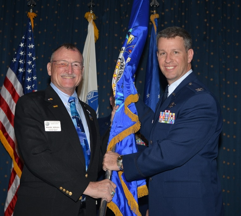 Vietnam veteran Roger Newell, city of Albuquerque veteran's liaison, receives a guidon from Col. Robert Reynor, 150th Special Operations Wing commander. Newell, an honorary commander in the wing, is promoting the importance of support veterans, especially March 29, which is Vietnam Veterans Day.