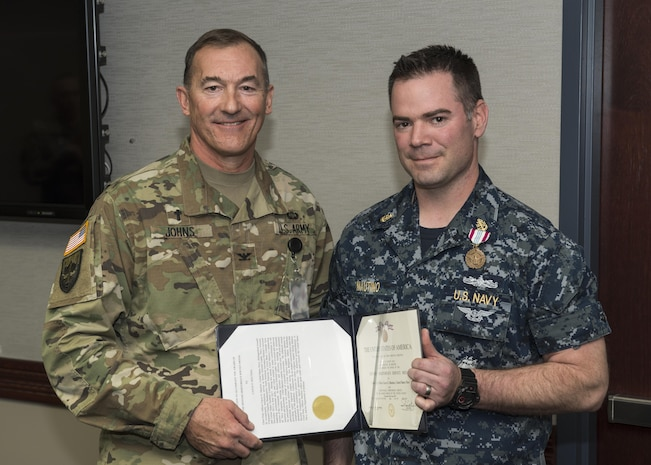 "COL Jay Johns III, NORAD and USNORTHCOM command chaplain, presents the Defense Meritorious Service Medal to Chief Petty Officer Cayce Mautino, U.S. Navy. The NORAD and USNORTHCOM Office of the Command Chaplain at held a religious affairs workshop titled  ""Embracing Complexity-Navigating Uncertainty"" March 23, 2017. The three-day event focused on strengthening relationships and interoperability with military mission partners. Attendees included the National Guard, National Guard Bureau, the Royal Bahamas Defence Force Command Chaplain, Canadian Armed Forces Chaplain General Representative, NORAD & USNORTHCOM Region, and Component and Subordinate Command Chaplains."