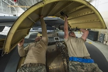 (From left) Senior Airman Allan Jungst and Staff Sgt. Alex Yount, 5th Maintenance Squadron crew chiefs, rotate an upper wrap cowling at Minot Air Force Base, N.D., March 20, 2017. During a phase inspection for 18 consecutive days, these maintainers wash, lubricate, inspect and fix all identified discrepancies on the B-52H Stratofortress. (U.S. Air Force photo/Airman 1st Class Jonathan McElderry)