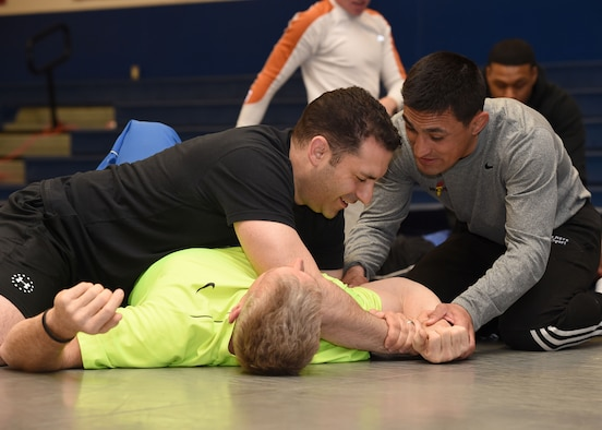 SCHRIEVER AIR FORCE BASE, Colo.— Marco Lara, lead combative class instructor provides instruction to Jason Janaros, as he grapples with Adam Edwards, during a combative class at Schriever Air Force Base, Colorado, Wednesday, March 29, 2017. The hourlong class covered basic mount and guard positioning, arm bar, bent arm bar and rear naked chokes submissions. (U.S. Air Force photo/Staff Sgt. Matthew Coleman-Foster)