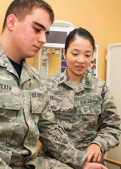 Capt. (Dr.) Thanh Thao Le, a family medicine physician assigned to the 66th Medical Squadron, checks the pulse of Senior Airman Chad A. Stricker, Jr., at the Hanscom Air Force Base, Mass., clinic March 24. Le moved from Vietnam to the United States with her family when she was 12-years old through a U.S. government program for former South Vietnamese officials. (U.S. Air Force photo by Walter Santos)