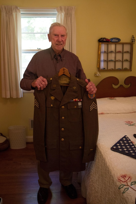 William Dellinger, a 96-year-old veteran and native of Charlotte North Carolina reminisces on events during WWII, things he's seen and the life he has lead, at his home Wednesday, Nov 2. Dellinger poses with his dress uniform. (U.S. Army Photo by Spc. Tynisha Daniel, 108th Training Command)