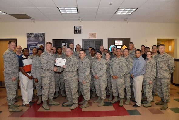 "Staff Sgt. Shaun Jackson, 47th Security Forces Squadron unit training section NCO in charge (center), accepts the ""XLer of the Week"" award from Col. Thomas Shank, 47th Flying Training Wing commander (left), and Chief Master Sgt. George Richey, 47th FTW command chief (right), on Laughlin Air Force Base, Texas, March 22, 2017. The XLer is a weekly award chosen by wing leadership and is presented to those who consistently make outstanding contributions to their unit and Laughlin. (U.S. Air Force photo/Airman 1st Class Daniel Hambor)"