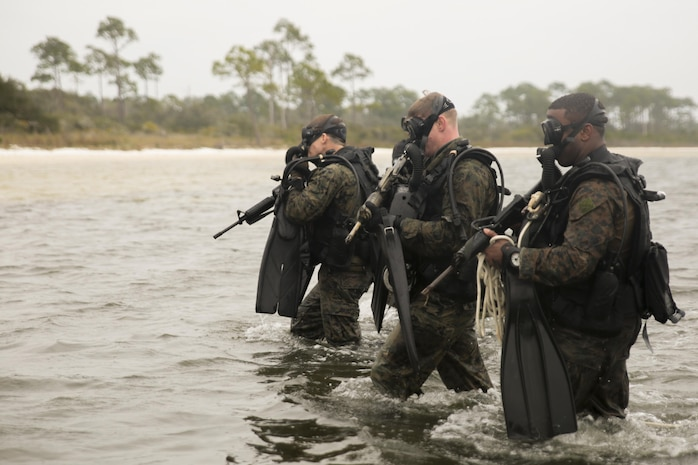 Staff Sgt. Daniel Franklin (left), team leader, Staff Sgt. Jamie Gill (center), team leader and Sgt. George Williams (right), assistant team leader with 3rd Force Reconnaissance Company, 4th Marine division exit the water during a ship-to-shore diving operation exercise at Pensacola, Fla., March 23, 2017. The exercise focused on performing sustainment training on Marine combative dive tactics. The training will enhance the company's capability conduct specialized insertion and extraction tasks. (U.S. Marine Corps photo by Sgt. Ian Ferro)