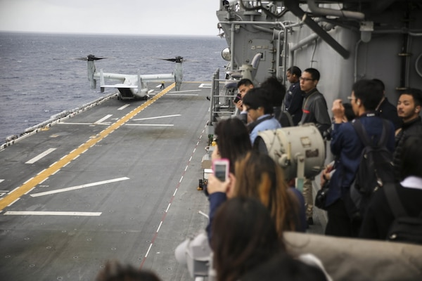 College students from Okinawa, Japan watch a Marine MV-22B Osprey land aboard the USS Bonhomme Richard (LHD 6) in the Pacific Ocean, March 25, 2017. College students from Okinawa International University, Ryukyu University and Toyo Medical Community College toured the USS Bonhomme Richard (LHD 6) as part of a military exchange experience during the 31st Marine Expeditionary Unit's 17.1 Spring Patrol of the Indo-Asia-Pacific region. Education programs, such as this military exchange experience, increase cooperation, trust and understanding between the U.S. military and the Okinawan community. As the Marine Corps' only continuously forward deployed unit, the 31st Marine Expeditionary Unit's air-ground-logistics team provides a flexible force, ready to perform a wide range of military operations, from limited combat to humanitarian assistance operations, throughout the Asia-Pacific region.
