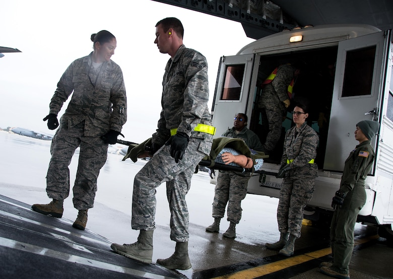 Patriot Delta participants carry a litter with a medical manikin patient off of an ambulance bus onto a C-17 Globemaster III during Patriot Delta at Travis Air Force Base, Calif. on March 24, 2017. Patriot Delta brought in aeromedical evacuations squadrons from the from the 911th Airlift Wing at Pittsburgh Air Reserve Station, Penn., the 908th AW at Maxwell Air Force Base, Miss.; the 932d Airlift Wing at Scott AFB, Ill.; and the 349th Air Mobility Wing at Travis AFB. (U.S. Air Force photo by Staff Sgt. Daniel Phelps)