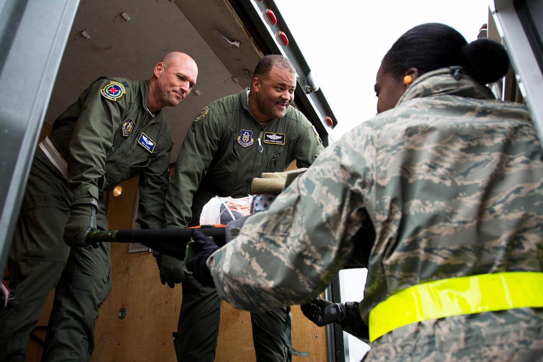 Capt. Erik Spiess, 349th Aeromedical Evacuations Squadron flight nurse, and Master Sgt. Rard Perkins, 911th Operations Group aircrew trainer, hand off a patient to members of the 60th Inpatient Squadron to secure on an ambulance bus for delivery to David Grant U.S. Air Force Medical Center at Travis Air Force Base, Calif., on March 24, 2017. Members of the 60th IPTS participated in the Air Force Reserve exercise Patriot Delta, providing enroute patient care and staging the medical manikins. (U.S. Air Force photo by Staff Sgt. Daniel Phelps)