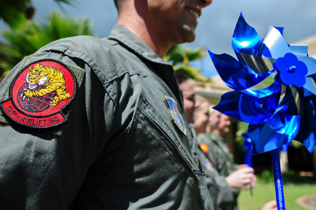 Members of the 535th Airlift Squadron gather together to show their support of National Child Abuse Prevention Month, at Joint Base Pearl Harbor-Hickam, Hawaii, March 29, 2017.  April was designated as National Child Abuse Prevention Month in 1983, acknowledge the importance of families and communities working together to prevent child abuse and neglect, and to promote the social and emotional well-being of children and families. (U.S. Air Force photo by Tech. Sgt. Heather Redman)