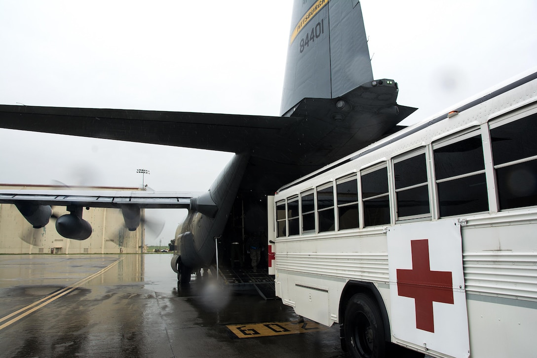 An ambulance bus from the 60th Inpatient Squadron backs up to a C-130 Hercules from Pittsburgh Air Reserve Station, Pennsylvania, during Patriot Delta at Travis Air Force Base, California, March 24, 2017. (U.S. Air Force photo by Staff Sgt. Daniel Phelps)