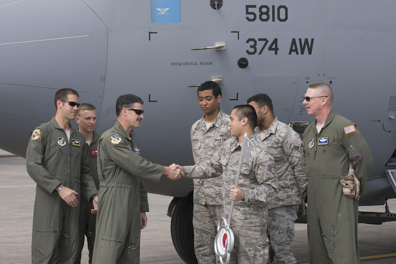 Col. Robert Dotson, 374th Operations Group commander, and Staff Sgt. Raymond Malig, 374th Aircraft Maintenance Squadron crew chief, shake hands in front of a C-130J Super Hercules at Yokota Air Base, Japan, March 29, 2017. Yokota serves as the primary Western Pacific airlift hub for U.S. Air Force peacetime and contingency operations. Missions included tactical air land, airdrop, aeromedical evacuation, special operations and distinguished visitor airlift. (U.S. Air Force photo by Yasuo Osakabe)
