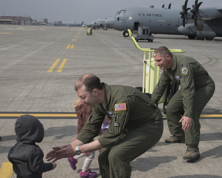 (Left to right) Tech. Sgt. Michael McArty, 374th Operations Group C-130 standardization and evaluation loadmaster, and Lt. Col. Robert Cureton, 374th Airlift Wing C-130J pilot, greet their children after landing at Yokota Air Base, Japan, March 29, 2017. This is the second C-130J delivered from Lockheed Martin, less than a month after the first was delivered March 6th. (U.S. Air Force photo by Yasuo Osakabe)