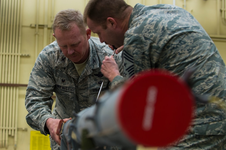 "U.S. Air Force Col. Joseph McFall, 52nd Fighter Wing command and Chief Master Sgt. Edwin Ludwigsen, 52nd FW command chief, build an Air Intercept Missile 9 during a Saber leadership ""out and about"" event at Spandgdahlem Air Base, Germany, March 27, 2017. The 52nd Maintenance Squadron munitions section provides all explosives to the 52nd FW to include missiles, guided bombs, 20 mm gun ammo, chaff/flare, countermeasures and practice bomb dummy unit 33 bombs.(U.S. Air Force photo by Senior Airman Dawn M. Weber)"