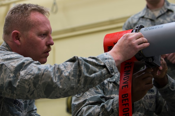 """U.S. Air Force Col. Joseph McFall, 52nd Fighter Wing commander, secures components to an Air Intercept Missile 9 at during a Saber leadership """"out and about"""" event Spangdahlem Air Base, Germany, March 27, 2017. The leadership team visited the 52nd Maintenance Squadron munitions section to learn the basics of munitions building and how pilots use them during flight. (U.S. Air Force photo by Senior Airman Dawn M. Weber)"""