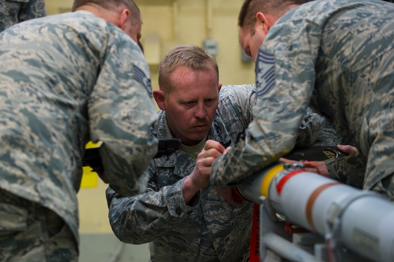 """U.S. Air Force Col. Joseph McFall, 52nd Fighter Wing commander, assisted by Chief Master Sgt. Edwin Ludwigsen, 52nd FW command chief, builds an Air Intercept Missile 9 during a Saber leadership """"out and about"""" event at Spangdahlem Air Base, Germany, March 27, 2017. Wing leadership learned the full spectrum of munitions building to include, testing, inspection, configuration, maintenance, and transportation. (U.S. Air Force photo by Senior Airman Dawn M. Weber)"""