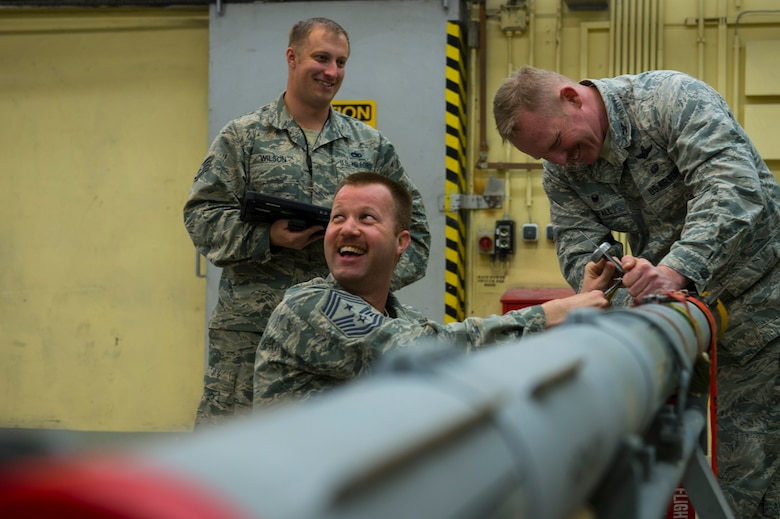 U.S. Air Force Chief Master Sgt. Edwin Ludwigsen 52nd Fighter Wing command chief and Col. Joseph McFall, 52nd FW commander, secure attachments to an Air Intercept Missile 9 at Spangdahlem Air Base, Germany, March 27, 2017. Airmen from the 52nd Maintenance Squadron munitions section work around the clock to support day-to-day flying.(U.S. Air Force photo by Senior Airman Dawn M. Weber)