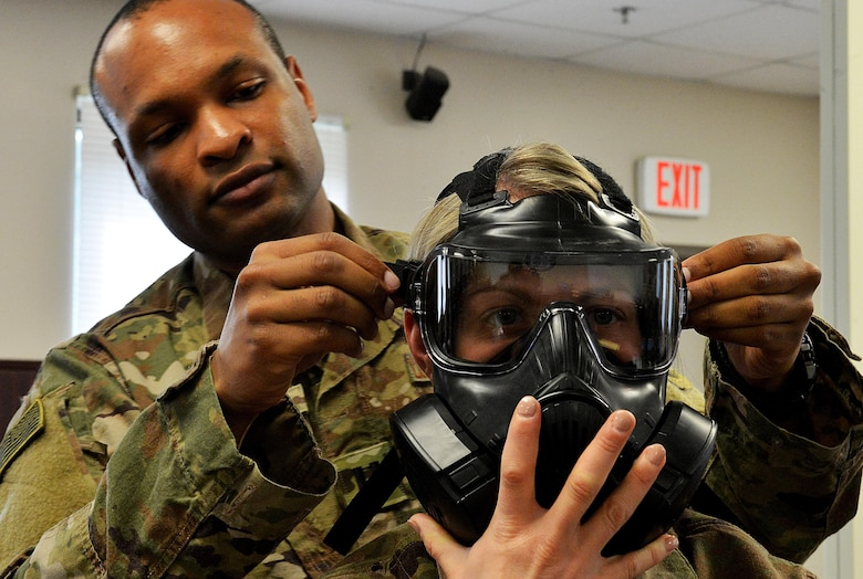 Capt. Matthew Thomas, Air Force Joint Test Program Office lead operation research systems analyst from Nellis Air Force Base, Nev., adjusts the gas mask of Master Sgt. Amanda Simonsen, 627th Civil Engineer Squadron commanders support staff section chief from Joint Base Lewis-McChord, Wash., during a chemical warfare class at Shaw AFB, S.C., Feb. 21, 2017. As part of their third week of training, the Rear Mission Support Element course students complete individual readiness tasks including chemical warfare and small arms qualification. (U.S. Air Force photo by Senior Airman Diana M. Cossaboom)