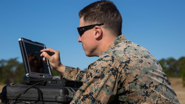 Sgt. Kyle Phillips configures computer equipment to ensure communications and controls connected to a Raven small unmanned aircraft system are working properly at Marine Corps Base Camp Lejeune, N.C., March 27, 2017. Marines conducted aerial training exercises at Tactical Landing Zone Dove to demonstrate the capabilities and build familiarization with the SUAS. Phillips is an intelligence specialist with 2nd Battalion, 8th Marine Regiment.