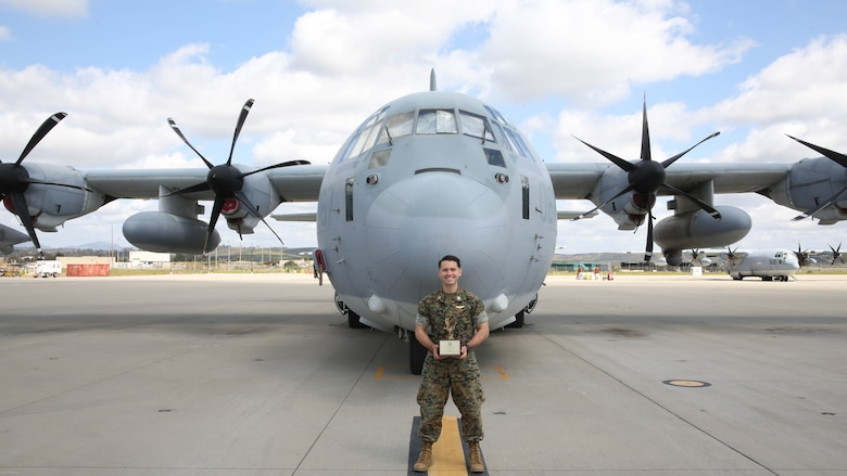 Capt. Christopher Lavergne, a KC-130J Super Hercules pilot with Marine Aerial Refueler Transport Squadron (VMGR) 352, proudly displays the 2017 Marine Corps Aviation Association Henry Wildfang award in front of a KC-130J at Marine Corps Air Station Miramar, Calif., March 27. VMGR-352 received the Henry Wildfang award for successful mission accomplishments and the most mishap free hours.
