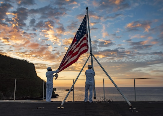 Navy Seaman Stephen Mugo and Petty Officer 3rd Class Jeremy Boling lower the U.S. flag at sunset during evening colors duty aboard the aircraft carrier USS Carl Vinson in Guam, Feb. 11, 2017. In April, the Navy will be the first service with access to the new online Servicemembers Group Life Insurance enrollment system. The new system will be available to the rest of the uniformed services later this year. Navy photo by Petty Officer 2nd Class Sean M. Castellano