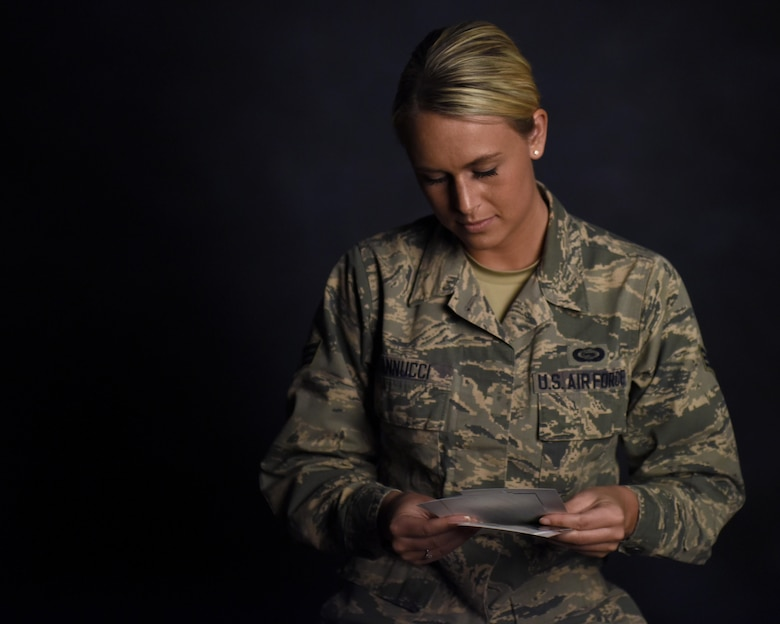U.S. Air Force Senior Airman Courtney Iannucci, an intelligence specialist assigned to the 180th Fighter Wing, looks through photos from her three-week volunteer trip to Ghana to care for orphans, March 12, 2017, at the 180FW. Airmen focus on service before self through volunteering in their communities both locally and globally. (U.S. Air National Guard photo by Airman Hope Geiger)