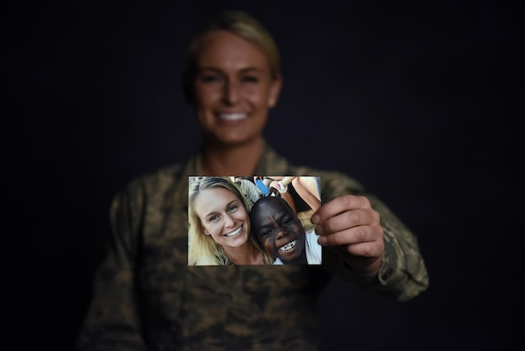 U.S. Air Force Senior Airman Courtney Iannucci, an intelligence specialist assigned to the 180th Fighter Wing, holds a photo up from her volunteer mission to Ghana to care for orphans, March 12, 2017, at the 180FW. 180FW Airmen are dedicated to selfless sacrifice and embodies the core values of the U.S. Air Force. (U.S. Air National Guard photo by Airman Hope Geiger)