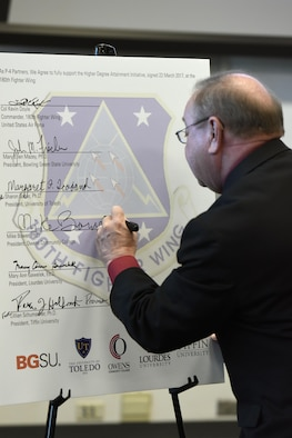 Mike Bower, president of Owens Community College, signs the Higher Degree Attainment Initiative March 22,2017 at the 180th Fighter Wing in Swanton, Ohio. The agreement between the 180FW and five local-area universities provides additional education opportunities for 180FW Airmen while providing participating colleges with recruitment opportunities. (U.S. Air National Guard photo by Staff Sgt. Shane Hughes)