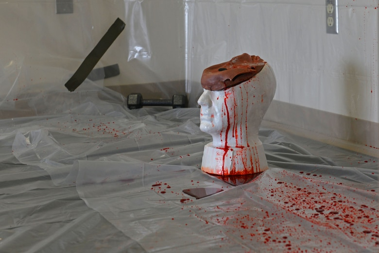 A replica head sits on the floor after being hit with a baseball bat and a gun several times to determine blood patterns after a forensic science demonstration at Shaw Air Force Base, S.C., March 28, 2017. Blood patterns can be used to determine the angles of and the number of attacks at a crime scene. (U.S. Air Force photo by Airman 1st Class Destinee Sweeney)