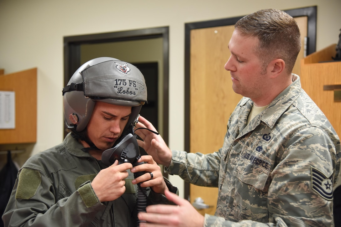 Tech. Sgt. Josh Frock,114th Operations Group aircrew flight equipment technician, assists Professional Bull Rider, Stetson Lawrence, with adjustments to his helmet and other protective equipment prior to an F-16 orientation flight at Joe Foss Field, S.D., March 29, 2017. The PBR organization visited the 114th Fighter Wing as a part of a community outreach program. (Air National Guard photo by Staff Sgt. Duane Duimstra/Released)