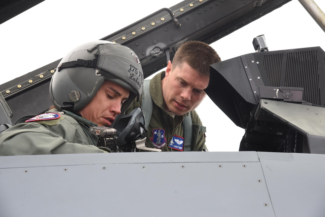 Capt. Casey Minor, 175th Fighter Squadron pilot, explains the controls and instruments of the F-16 to Professional Bull Rider, Stetson Lawrence, before his F-16 orientation ride at Joe Foss Field, S.D. on March 29, 2017. The PBR organization visited the 114th Fighter Wing as a part of a community outreach program. (Air National Guard photo by Staff Sgt. Duane Duimstra/Released)
