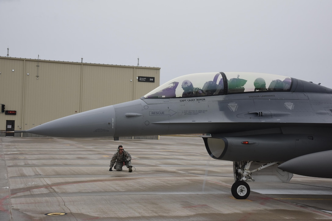 Master Sgt. Ryan Peskey, 114th Aircraft Maintenance crew chief, performs launch procedures on the F-16D used for the orientation flight with Professional Bull Rider, Stetson Lawrence, at Joe Foss Field, S.D. on March 29, 2017. The PBR organization visited the 114th Fighter Wing as a part of a community outreach program. (Air National Guard photo by Staff Sgt. Duane Duimstra/Released)