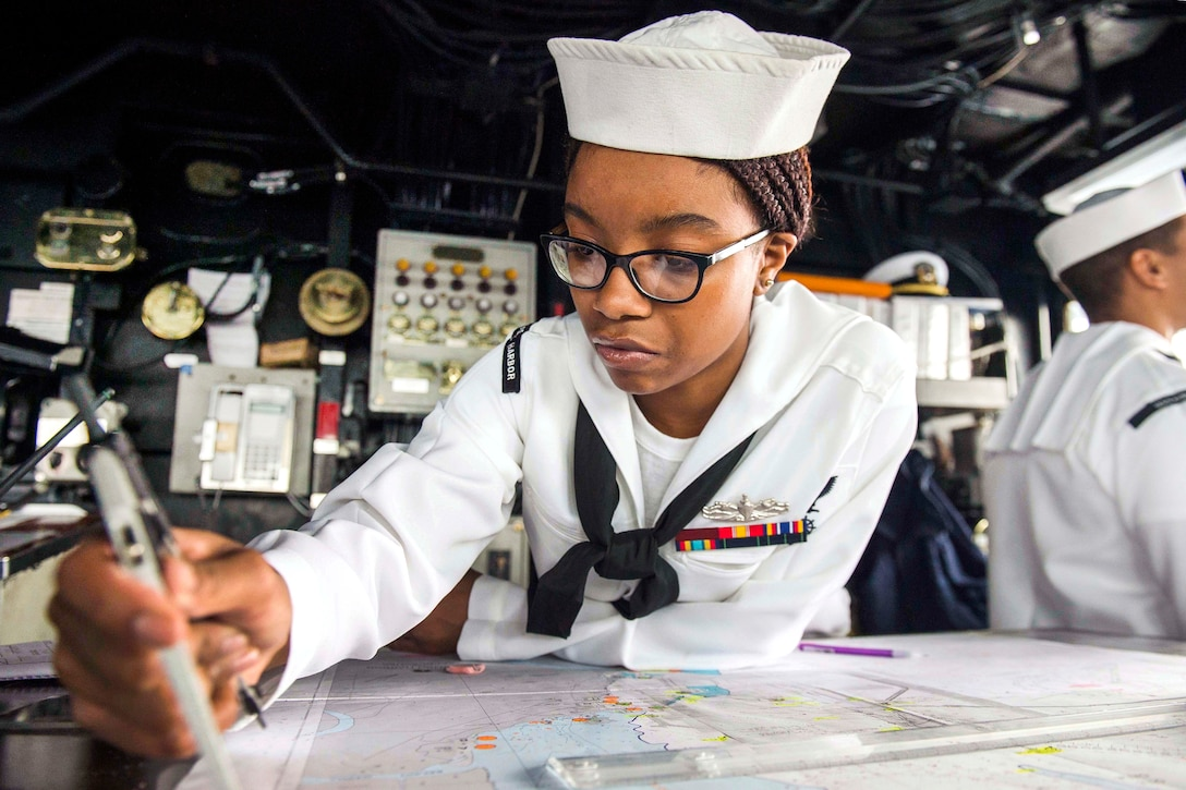 Navy Petty Officer 3rd Class Tyler Terrell plots a course during watch on the bridge of the amphibious dock landing ship USS Comstock.