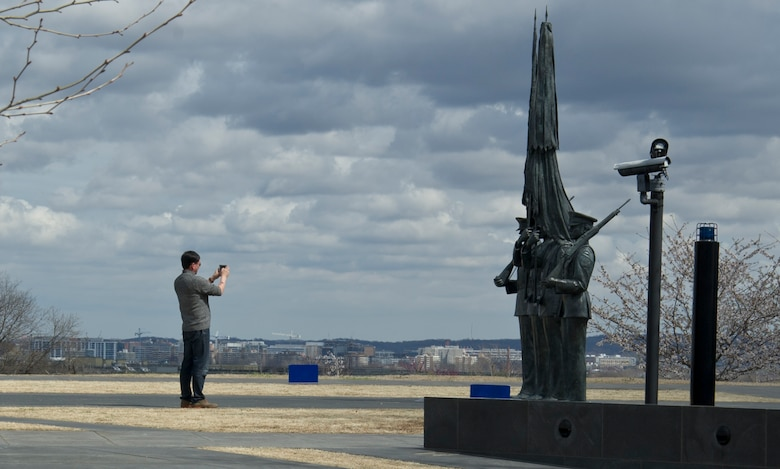 A visitor to the U.S. Air Force Memorial photographs statues that portray Airmen from The U.S. Air Force Honor Guard March 28, 2017 in Arlington, Virginia. The Air Force Memorial, located at 1 Air Force Memorial Way, is free and open to the public. (U.S. Air Force photo by Staff Sgt. Joe Yanik)