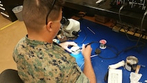 The Micro/Miniature Repair Course requires a steady hand and calm nerves in order to perform the necessary repairs on equipment.  Marines learn to perform component level repair on electronic components as small as one millimeter wide. Here, Lance Corporal Asencio, Jonathan R. performs eyelet repair under the watchful eye of his seasoned instructor, Staff Sergeant Cales, Noah M.