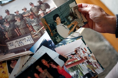 Iowa Army National Guard Chief Warrant Officer 5 Marty Hupp, of Grimes, Iowa, sorts through photographs from her 40-year military career in light of her upcoming retirement.
